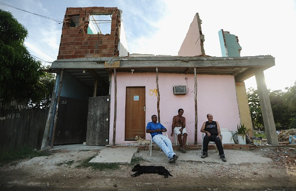 People sit beneath a partially demolished structure in Vila Autodromo. Credit: Mario Tama/Getty