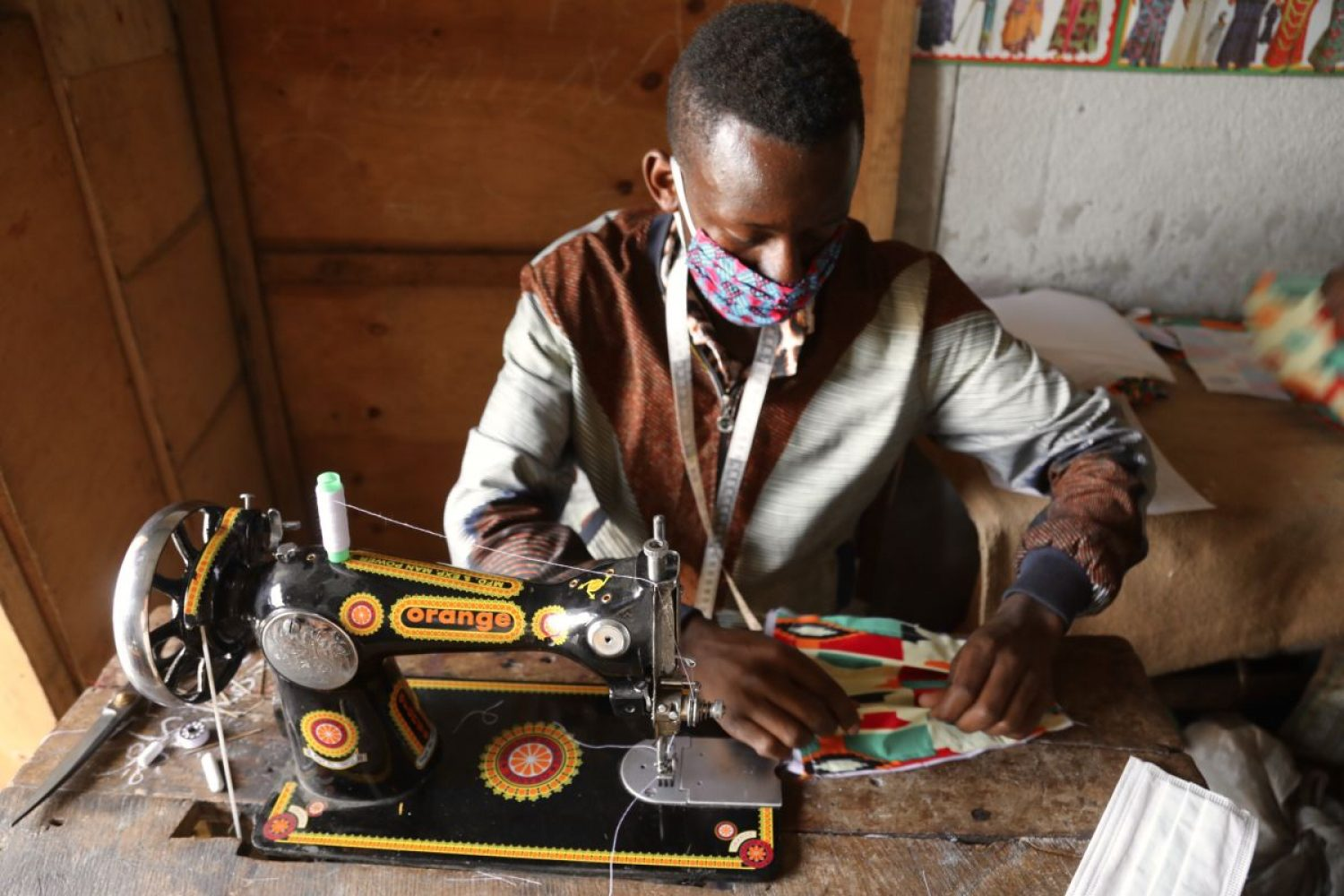 A tailor in Goma making a colourful face mask to help halt the spread of coronavirus