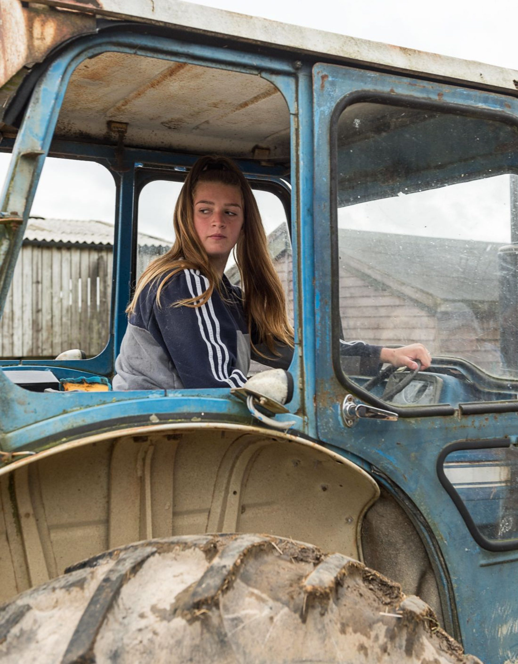 A young person learns to drive a tractor at Rylands Farm in Dorset