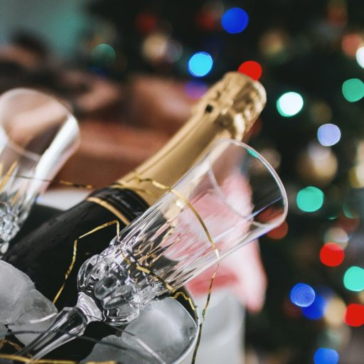 Champagne bottle in front of Christmas tree